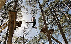 Kid swinging through ropes course